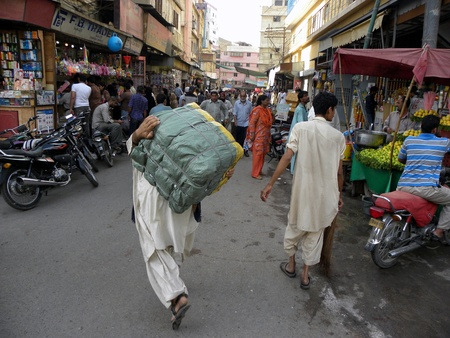 PAKISTANKARACHI_MAN CARRYING HEAVY LOAD OF GOODS ON HIS BACK IN THE BOLTAN MARKET TODAY ON 9 APRIL 2012