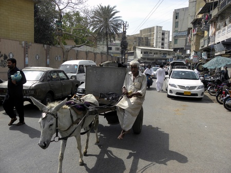 PAKISTANKARACHI_LOCAL DONKEY CART RIDER CARRIES DRINKING WATER TANK TO EARN HIS LIVELIHOOD FOR SUPPORT HIS FAMILY BY HIS DONKEY CART PASSES THROUGH A ROAD TODAY ON SATURDAY 14 APRIL 2012                              Editorial