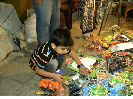 PAKISTANKARACHI_KID FINDS BEN 10 TOYS OF HIS CHOICE FROM FOOTPATH IN THE TARIQ ROAD TODAY ON MONDAY 16 APRIL 2012