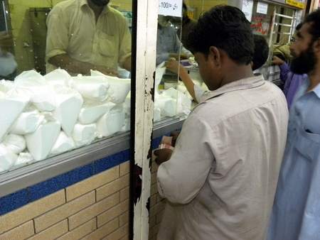 shop keeper: PAKISTANKARACHI_MAN COUNTING MONEY TO BUY MILK PACKET FROM MILK SHOP TODAY ON FRIDAY 20 APRIL 2012