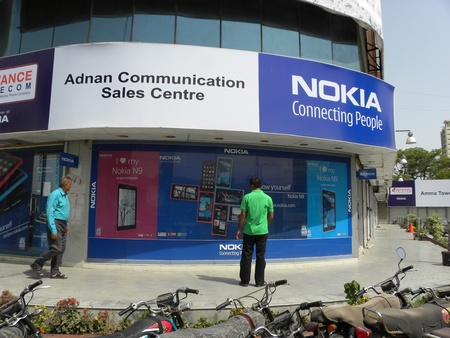 PAKSTANKARACHI_TWO MEN WATCHING POSTEROF  NOKIA NEW MOBILE PHONE NOKIA N9 AT NOKIA FRANCHISE SHOP WHILE PASSING THROUGH THE FOOTPATH TODAY ON SATURDAY 28 APRIL 2012 IN KARACHI AT SADDAR  Editorial