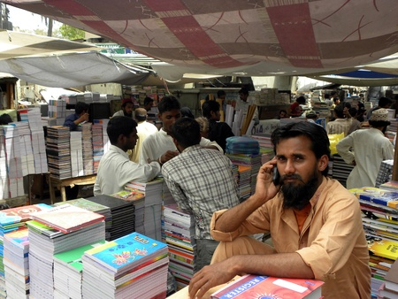 shop keeper: PAKISTANKARACHI_LOCAL SHOP KEEPER USING MOBILE PHONE  AND FACING AT CAMERA TODAY ON  MONDAY 30 APRIL 2012