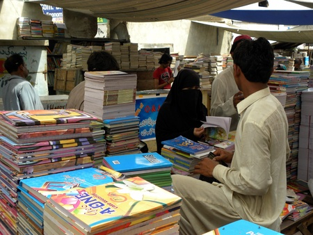 PAKSITANKARACHI_WOMAN IS CHECK COPY PAGES BEFORE BUYING COPY AT NOTE BOOK STALL TODAY ON MONDAY 30 APRIL 2012