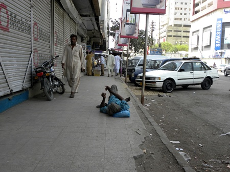 PAKISTANKARACHI_BEGGAR PRETENDS TO BE DISABLED ON THE SIDE OF THE ROAD