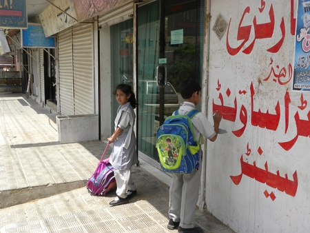 PAKISTANKARACHI_SCHOOL BOY WRITING SOMETHING  HEALTH CARE CLINIC WALL TODAY ON THURSDAY 10 MAY 2012 IN KARACHI