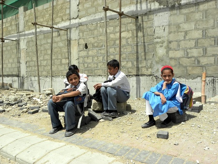 PAKISTANKARACHI_SCHOOL KIDS SITTING ON CONCRETE BLOCK DUE TO WARITING FOR BUS TODAY ON THURSDAY 10 MAY 2012 IN KARACHI