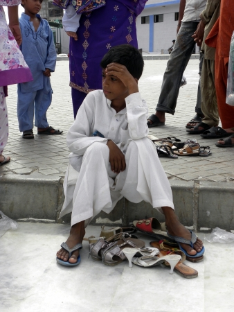 PAKISTANKARACHI_BOY SITTING ON GROUND DUE TO TAKING CARE OF HIS FAMILY SHOES TODAY ON FRIDAY 18 MAY 2012 IN KARACHI
