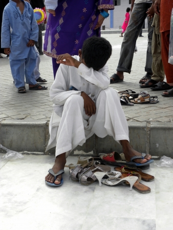 PAKISTANKARACHI_BOY SITTING ON GROUND DUE TO TAKING CARE OF HIS FAMILY SHOES TODAY ON FRIDAY 18 MAY 2012 IN KARACHI                                               Editorial