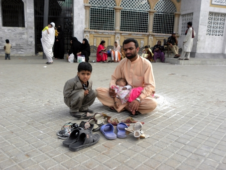 PAKISTANKARACHI_MAN SITTING DOWN ON GROUND WITH HIS CHILDREN FOR TAKING CARE OF HIS FAMILY MEMBER SHOES TODAY ON MONDAY 21 MAY 2012