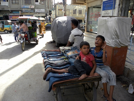 PAKISTANKARACHI_BOY SITTING ON HAND CART FOR SALE JEANS PANT WITH THEIR UNCLE,NOT SO MUCH EXPENSIVE FOR POOR PEOPLE TODAY ON MONDAY 28 MAY 2012 IN KARACHI,MEHMOODABAD                               Editorial