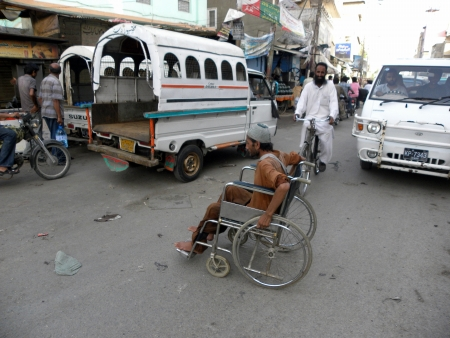 PAKISTANKARACHI_DISABLED MAN ON WHEELCHAIR FASTYCROSSING ROAD FROM HEAVY TRAFFIC WITHOUT STOPING ON ROAD TODAY ON SUNDAY SATURDAY 16 JUNE 2012 IN KARACHI