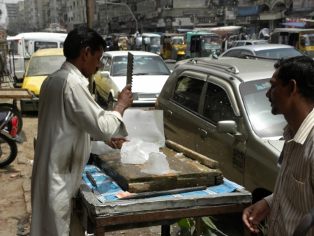 PAKISTANKARACHI_LOCAL MAN MAKING ICE PIECES FOR COUSTOMER BY HIS ICE CUTTING TOOL TODAY ON THURSDAY 21 JUNE 2012 IN KARACHI