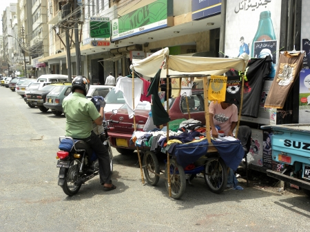 PAKISTANKARACHI_MAN ON BIKE TRYING TO BUY LOW PRICE OF T-SHIRT FROM HAND CART SHOP TODAY ON THURSDAY 21 JUNE 2012 IN KARACHI