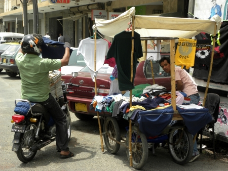 karachi: PAKISTANKARACHI_MAN ON BIKE TRYING TO BUY LOW PRICE OF T-SHIRT FROM HAND CART SHOP TODAY ON THURSDAY 21 JUNE 2012 IN KARACHI