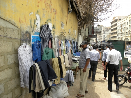 PAKISTANKARACHI_LOCAL PEOPLE CHECKING SHIRTS FROM FOOTPATH STALL TRYING TO BUY LOW PRICE SHIRTS ARE USED SHIRT TODAY ON FRIDAY 22 JUNE 2012