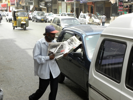 PAKISTANKARACHI_LOCAL NEWS PAPER MAN IS SALING NEWS PAPER AT TRAFFIC SIGNAL TODAY ON SUNDAY 24 JUNE 2012 IN KARACHI