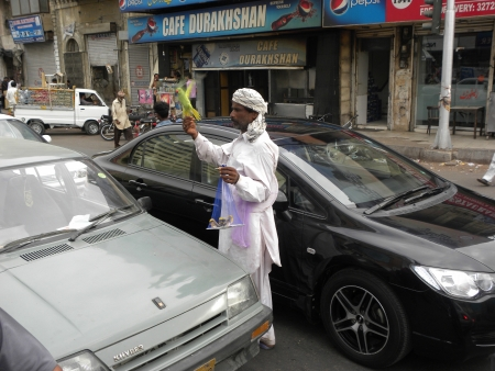 PAKISTANKARACHI_LOCAL ADULT MAN SELLING BIRDS AN GREEN PARROTS ON TRAFFIC SIGNAL IN HOLY MONTH OF RAMADAM, RAMADAM IS HOLIEST MONTH IN ISLAMIC CANLEDAR TODAY ON THURSDAY 26 JULY 2012 IN KARACHI