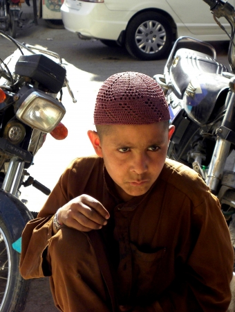 PAKISTANKARACHI_SMALL BOY WITH STARING FACE EXPRESSION WHILE SIITING SIDE OF THE ROAD TODAY ON THURSDAY 9 AUGUST 2012