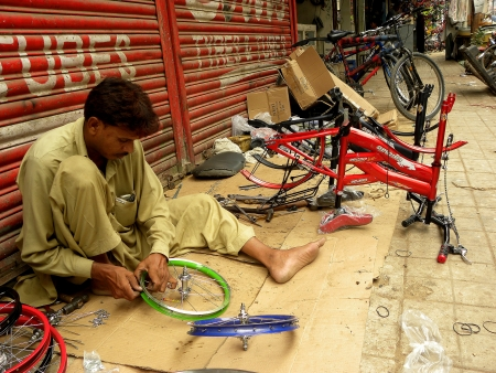 PAKISTANKARACHI_LOCAL MAN INSTALLING NEW CYCLE PARTS FOR BRAND NEW CYCLE TO SALE IN MARKET TODAY ON FRIDAY 10 AUGUST 2012 IN KARACHI LIGHT HOUSE