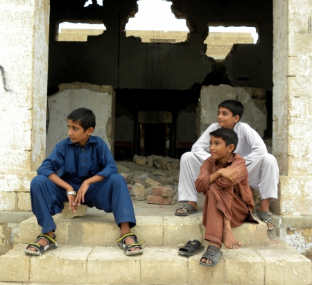 cricket game: PAKISTANKARACHI_THREE FRIENDS WATCHING OTHER BOY PLAYING CRICKET GAME IN GROUND TODAY ON SUNDAY 26 AUGUST 2012 IN KARACHI KALA PUL