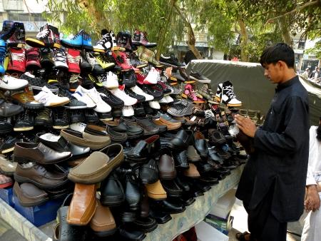 KARACHIPAKISTAN A BOY DOING FOOTWEAR BUSINESS ON SUNDAY 27 JANUARY 2013