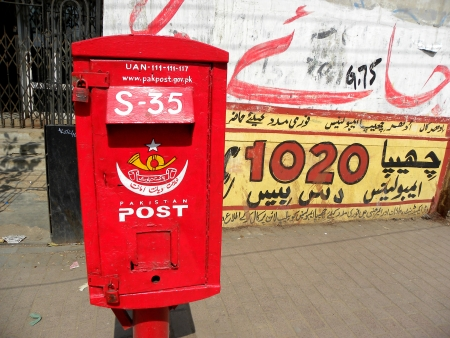 KARACHI, PAKISTAN : RED AND VINTAGE PAKISTANI POSTBOX (WITH WALL CHALKING BACKGROUND) HERE ON MONDAY 25 FEBRUARY 2013