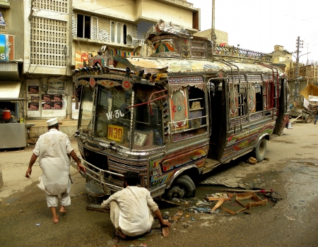 KARACHIPAKISTAN_LOCAL PASSENGER BUS GOT STUCK IN HOLE ,BUS DRIVER AND CONDUCTOR TRYING TO PULL OUT BUS FROM HOLE. ON A ROAD  IN MEHMOODABAD KARACHI HERE ON TUESDAY 9 APRIL 2013