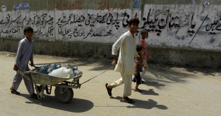 KARACHIPAKISTAN_ YOUNG BOYS PULLING HAND CART WHICH LOADED WITH WATER GALLONS GALLONS FILL WITH DRINKING WATER. HERE ON THURSDAY 9 MAY 2013