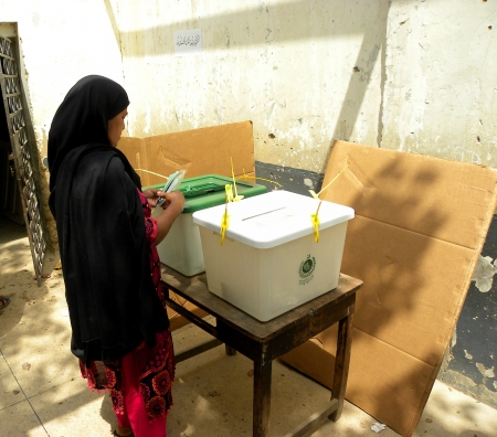 encuestando: MUJER QUE SE COLOCA AL LADO urnas para emitir su voto en el colegio electoral en Karachi, Pakist�n HOY EL S�BADO 11 MAY 2013