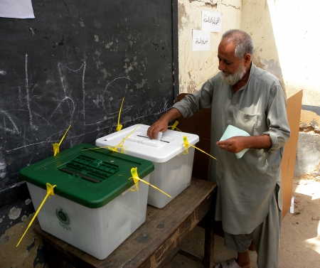 polling: ELDER MAN PUT HIS BALLOT PAPER IN BALLOT BOX AT POLLING STATION IN KARACHI,PAKISTAN TODAY ON SATURDAY 11 MAY 2013  Editorial