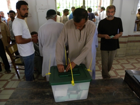karachi: MAN PUT HIS BALLOT PAPER IN BALLOT BOX AT POLLING STATION IN KARACHI,PAKISTAN TODAY ON SATURDAY 11 MAY 2013  Editorial