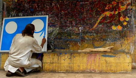 KARACHI:PAKISTAN_MATURE PAINTER BUSY IN HIS PAINTING ON BORAD, NEAR BANS ROAD KARACHI HERE ON THURSDAY 23 MAY 2013                                    Editorial