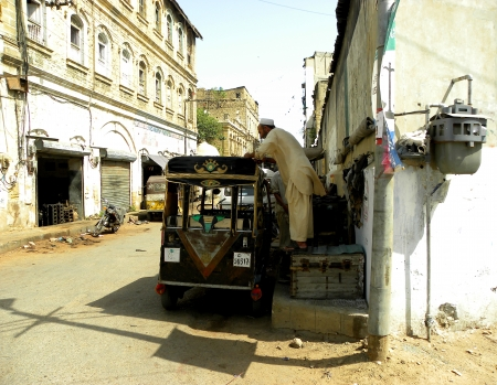 KARACHI:PAKISTAN_VERY TALENTED  SHOE COBBLER SEWING AUTO RICKSHAWS TOP ROOF HERE ON SATURDAY 25 MAY 2013                                   Editorial