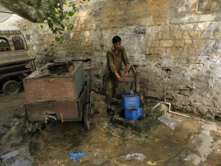 KARACHIPAKISTAN_PAKISTANI WATER DISBTRIBUTORUSING HAND PUMP TO FILL WATER TANK TO DISTRIBUT WATER TO CUSTOMER IN TIME HERE ON TUESDAY 18 JUNE 2013
