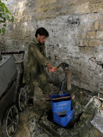 fill fill in: KARACHIPAKISTAN_PAKISTANI WATER DISBTRIBUTORUSING HAND PUMP TO FILL WATER TANK TO DISTRIBUT WATER TO CUSTOMER IN TIME HERE ON TUESDAY 18 JUNE 2013