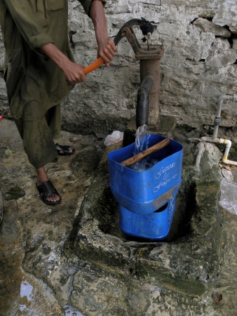 KARACHIPAKISTAN_PAKISTANI WATER DISBTRIBUTOR USING HAND PUMP TO FILL WATER TANK TO DISTRIBUT WATER TO CUSTOMER IN TIME HERE ON TUESDAY 18 JUNE 2013                                Editorial