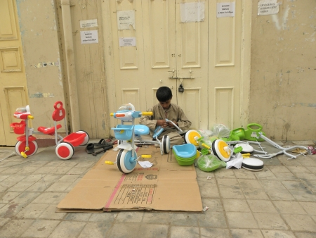 KARACHIPAKISTAN_PAKISTANI YOUNG BOY BUSY IN ASSEMBLING BICYCLE PARTS ON A ROADSIDE HERE ON WEDNESDAY 19 JUNE 2013 Editorial