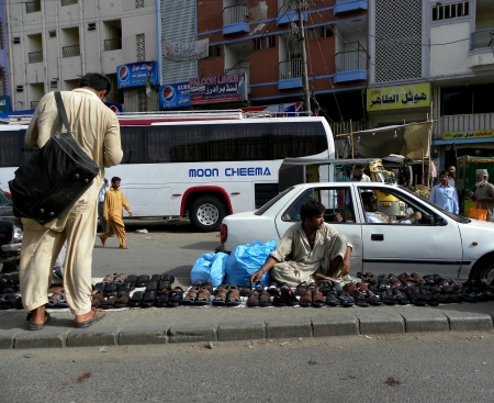 Pakistani traveler watching clobber shoe on the road. Editorial
