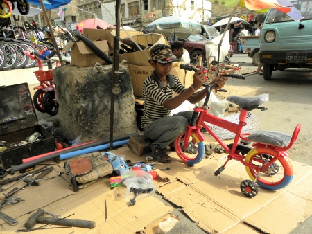 KARACHIPAKISTAN_PAKISTANI YOUNG BOY REPARING BICYCLE PARTS ON A ROADSIDE HERE ON WEDNESDAY 19 JUNE 2013  Editorial