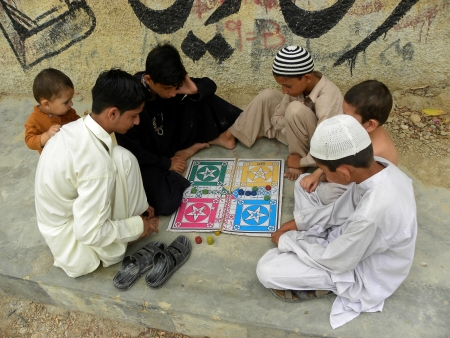 KARACHIPAKISTAN_PASHTUN BOYS PLAYING LUDO GAME WHILE THEY DONT HAVE ACCESS TO MODERN VIDEO GAMES DUE TO ECONOMIC PROBLEMS IN POVERTY