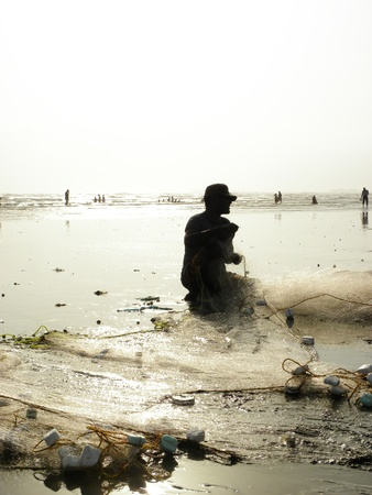 KARACHI PAKISTAN_FISHERMAN COLLECTING FISH FROM FISH NET AT SEA VIEW CLIFTON BEACH KARACHI WEDNESDAY 28 AUGUST 2013