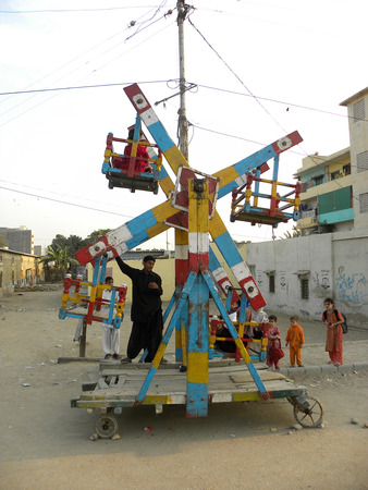 KARACHI PAKISTAN_KIDS ENJOYING THEIR FOVOURITE RIDE NEAR THEIR HOME IN STREET HERE ON MONDAY 25 NOVOENBER 2013