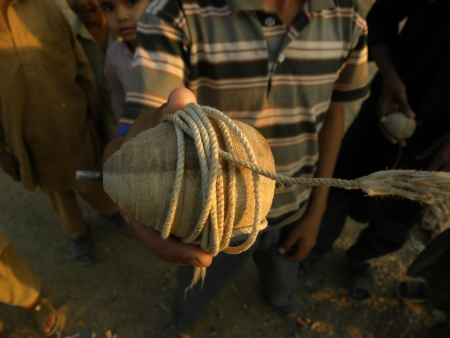 karachi pakistan_a young boys hold in his hand spintop spintop is traditional game in pakistan for young kindstop designed to be spun rapidly on the ground Traditionally tops were constructed of wood, sometimes with an iron tip, and would be set in motion