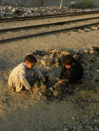 KARACHI PAKISTAN_TWO YOUNG BOYS PLAYING WITH STONES ON GROUND HERE ON THURSDAY 5 DECEMBER 2013