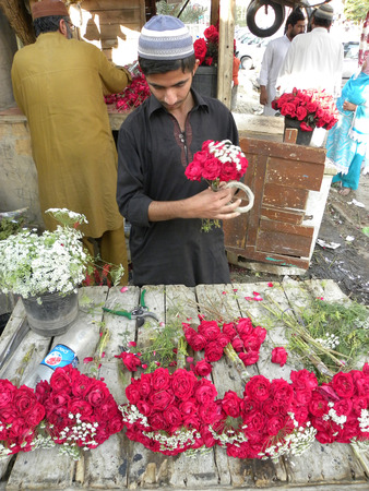 karachi: KARACHI PAKISTAN_YOUNG BOY MAKING FRESH RED ROSES  OF BOUQET ON VALENTINES DAY ROSES ARE ANCIENT SYMBOLS OF LOVE AND BEAUTY HERE ON FRIDAY 14 FEBRUARY 2014