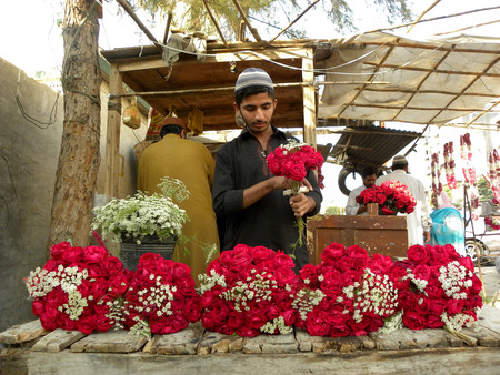 KARACHI PAKISTAN_YOUNG BOY MAKING FRESH RED ROSES  OF BOUQET ON VALENTINES DAY ROSES ARE ANCIENT SYMBOLS OF LOVE AND BEAUTY HERE ON FRIDAY 14 FEBRUARY 2014