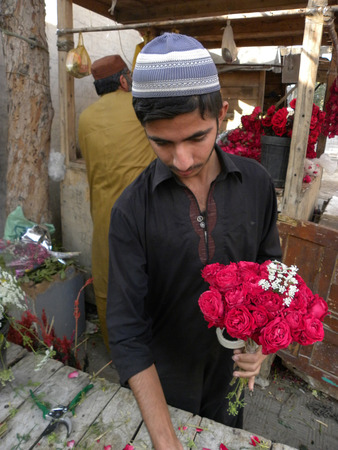 YKAACHI PAKISAN_YOUNG BOY HOLDS  FRESH RED ROSES OF BOUQET IN HIS HAND ON VALENTINES DAY ROSES ARE ANCIENT SYMBOLS OF LOVE AND BEAUTY HERE ON RIDAY 14 FEBRUARY 2014