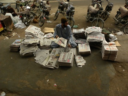 KARACHI PAKISTAN_ FRIDAY ,4 APRIAL 2014 Newspaper distributors sorting news papers at newspaper distribution point  Newspaper distributors sorting news papers at newspaper distribution point, A newspaper is a scheduled publication containing news of curre