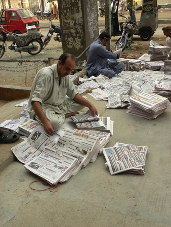 karachi: KARACHI PAKISTAN_ FRIDAY ,4 APRIAL 2014 Newspaper distributors sorting news papers at newspaper distribution point  Newspaper distributors sorting news papers at newspaper distribution point, A newspaper is a scheduled publication containing news of curre