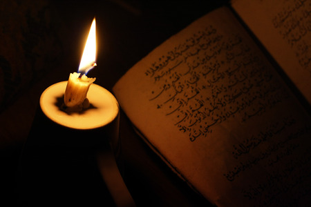 enlightment: arabic book with light candle